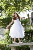 Schönes Kind im weißen Kleid, das im Park spielt Stockfotografie