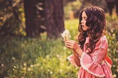 Schönes Kindermädchen gekleidet als Märchenprinzessin, die mit Schlagball im Sommerwald spielt Lizenzfreies Stockbild