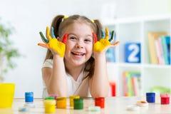 Schönes Kindermädchen mit den Händen in den Farbfarben Stockfoto