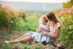 Schönes Kindermädchen mit junger Mutter tragen die zufällige Kleidung, die in einem Garten mit rosa Blütenrosen sitzt stockfotos