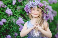 Schönes Kindermädchen mit Kranz von lila Blumen Lizenzfreie Stockfotografie