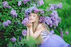 Schönes Kindermädchen mit Kranz von lila Blumen Stockbilder