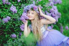 Schönes Kindermädchen mit Kranz von lila Blumen Stockbild