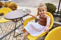 Schönes Kleid der Abnutzung des kleinen Mädchens in Mode, das in einem Café sitzt Stockfotos