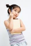 Schönes kleines asiatisches Mädchen, das mit Bleistift und Notizbuch denkt Stockfotos