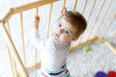 Schönes kleines Baby, das inneren Laufstall steht Nettes entzückendes Kind, das mit buntem Spielzeug spielt lizenzfreie stockbilder