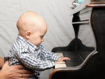 Schönes kleines Baby spielt Klavier Lizenzfreie Stockbilder