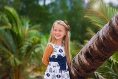 Schönes kleines blondes Mädchen mit dem langen Haar steht nahe bei Palmen auf dem Strand am Abend bei Sonnenuntergang Das Konzept Stockfotos