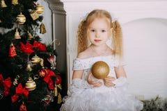 Schönes kleines blondes Mädchen mit Weihnachtsball Stockbild