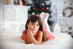 Schönes kleines Brunettemädchen, das auf ein Wunder in Christma wartet lizenzfreie stockbilder