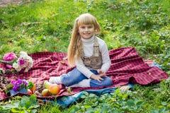 Schönes kleines junges Baby, das auf einem roten Plaid sitzt Reizendes Kind, das mit hellen Blumen lächelt Stockbild