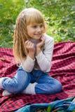Schönes kleines junges Baby, das auf einem roten Plaid sitzt Reizendes Kind, das mit hellen Blumen lächelt Stockfoto