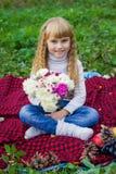 Schönes kleines junges Baby, das auf einem roten Plaid sitzt Reizendes Kind, das mit hellen Blumen lächelt Lizenzfreies Stockfoto