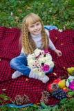 Schönes kleines junges Baby, das auf einem roten Plaid sitzt Reizendes Kind, das mit hellen Blumen lächelt Lizenzfreie Stockbilder