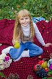 Schönes kleines junges Baby in einem rosa Hut mit Birne in der Hand Schönes Kind, das auf einem roten Plaid sitzt Stockfoto