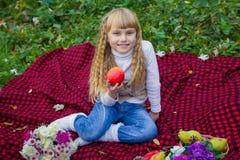 Schönes kleines junges Baby in einem rosa Hut mit einem Apfel in seiner Hand Schönes Kind, das auf einem roten Plaid sitzt Stockbild