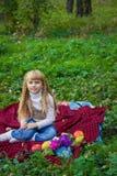 Schönes kleines junges Baby in einem rosa Hut mit einem Apfel in seiner Hand Schönes Kind, das auf einem roten Plaid sitzt Lizenzfreies Stockfoto
