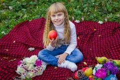 Schönes kleines junges Baby in einem rosa Hut mit einem Apfel in seiner Hand Schönes Kind, das auf einem roten Plaid sitzt Lizenzfreie Stockfotos
