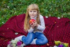 Schönes kleines junges Baby in einem rosa Hut mit einem Apfel in seiner Hand Schönes Kind, das auf einem roten Plaid sitzt Lizenzfreies Stockbild