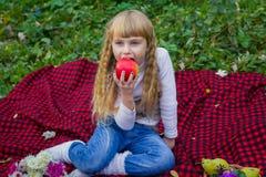 Schönes kleines junges Baby in einem rosa Hut mit einem Apfel in seiner Hand Schönes Kind, das auf einem roten Plaid sitzt Lizenzfreie Stockbilder