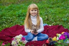 Schönes kleines junges Baby in einem rosa Hut mit einem Klumpen in seinen Händen Schönes Kind, das auf einem roten Plaid sitzt Lizenzfreies Stockbild