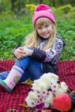Schönes kleines junges Baby in einem rosa Hut Schönes Kind, das auf einem roten Plaid sitzt Stockfoto