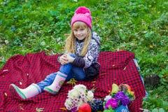 Schönes kleines junges Baby in einem rosa Hut Schönes Kind, das auf einem roten Plaid sitzt Lizenzfreies Stockfoto