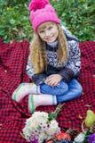 Schönes kleines junges Baby in einem rosa Hut Schönes Kind, das auf einem roten Plaid sitzt Lizenzfreie Stockbilder