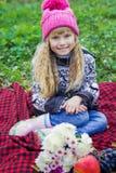 Schönes kleines junges Baby in einem rosa Hut Schönes Kind, das auf einem roten Plaid sitzt Lizenzfreies Stockbild