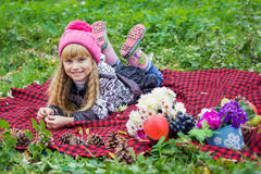Schönes kleines junges Baby in einem rosa Hut Schönes Kind liegt auf einem roten Plaid Lizenzfreie Stockfotos