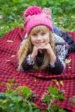 Schönes kleines junges Baby in einem rosa Hut Schönes Kind liegt auf einem roten Plaid Stockbilder