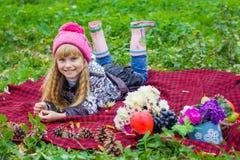 Schönes kleines junges Baby in einem rosa Hut Schönes Kind liegt auf einem roten Plaid Stockfoto