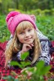 Schönes kleines junges Baby in einem rosa Hut Schönes Kind liegt auf einem roten Plaid Stockbild