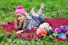 Schönes kleines junges Baby in einem rosa Hut Schönes Kind liegt auf einem roten Plaid Lizenzfreie Stockfotografie