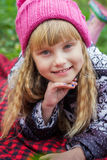 Schönes kleines junges Baby in einem rosa Hut Schönes Kind liegt auf einem roten Plaid Lizenzfreies Stockbild
