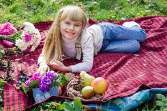 Schönes kleines junges Baby liegt auf einem roten Plaid Reizendes Kind, das mit hellen Blumen lächelt Stockfoto
