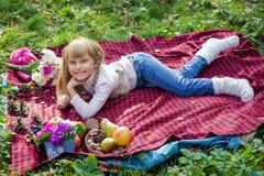 Schönes kleines junges Baby liegt auf einem roten Plaid Reizendes Kind, das mit hellen Blumen lächelt Stockfotografie