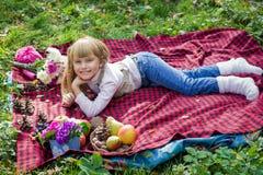 Schönes kleines junges Baby liegt auf einem roten Plaid Reizendes Kind, das mit hellen Blumen lächelt Stockbild