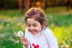 Schönes kleines Kind mit Löwenzahnblume in der sonnigen Sommergleichheit stockfotografie