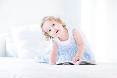 Schönes kleines Kleinkindmädchen mit Buch des gelockten Haares Lese Lizenzfreie Stockfotos