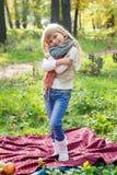 Schönes kleines langhaariges blondes Mädchen, das in einem grünen Park und in einem Lächeln steht Lizenzfreies Stockbild