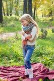 Schönes kleines langhaariges blondes Mädchen, das in einem grünen Park und in einem Lächeln steht Stockfotografie