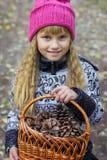 Schönes kleines langhaariges blondes Mädchen, das in einem grünen Park und in einem Lächeln steht Stockfoto