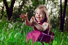Schönes kleines Mädchen auf einem Rasen mit Löwenzahn Lizenzfreie Stockfotos