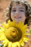 Schönes kleines Mädchen auf einem Sommersonnenblumegebiet Lizenzfreie Stockfotografie