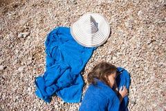 Schönes kleines Mädchen, das auf dem Strand eingewickelt im blauen Tuch nahe weißem Hut liegt Stockbilder