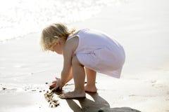 Schönes kleines Mädchen, das auf dem Strand spielt Stockbild