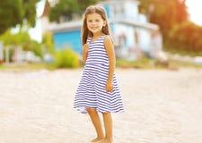 Schönes kleines Mädchen, das auf dem Strand stillsteht Stockfotos