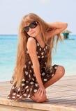 Schönes kleines Mädchen, das auf der Sonneplattform aufwirft Lizenzfreies Stockfoto