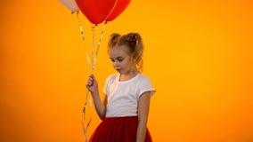 Schönes kleines Mädchen, das Ballone hält und, jugendliches Kindergefühl schüchtern denkt lizenzfreie stockfotos